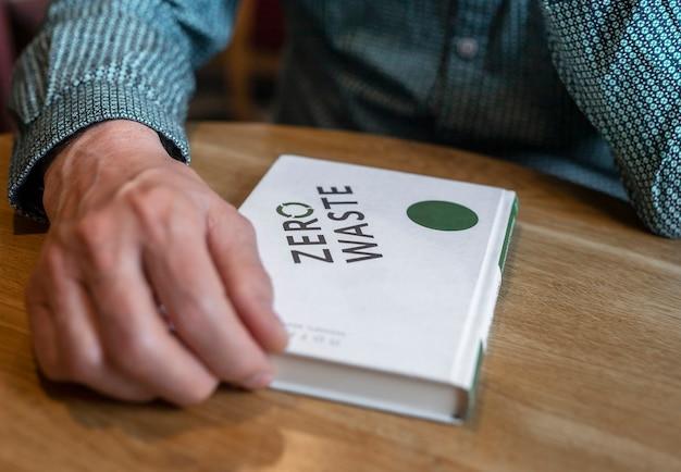 Homme lisant un livre zéro déchet au café, gros plan. concept d'éducation écologique.