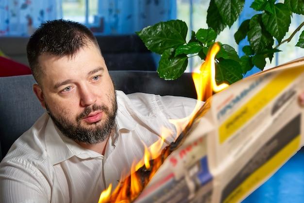 Homme lisant des nouvelles dans le journal brûlant.