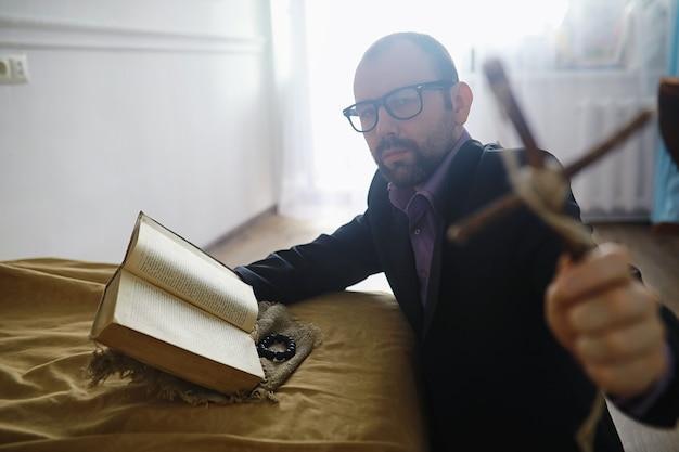 Homme lisant et priant de la sainte bible près du lit le soir. chrétiens et concept d'étude de la bible. étudier la parole de dieu à l'église.