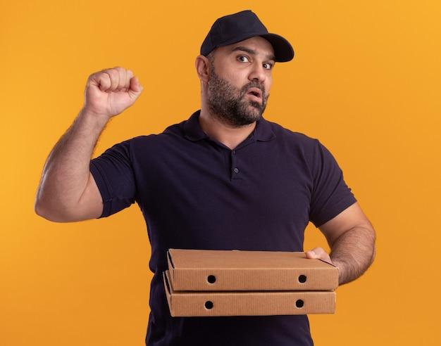 Homme de livraison d'âge moyen confus en uniforme et cap tenant des boîtes de pizza montrant oui geste isolé sur mur jaune