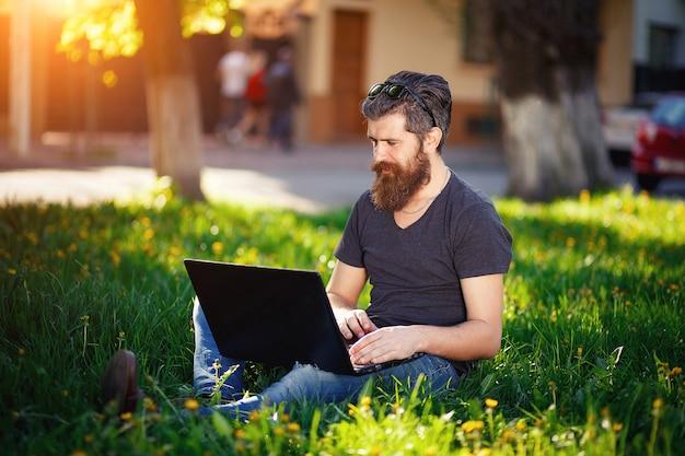 Un homme avec une longue barbe et des cheveux épais dans une chemise et un jean est assis sur l'herbe verte avec un ordinateur portable dans ses mains au coucher du soleil