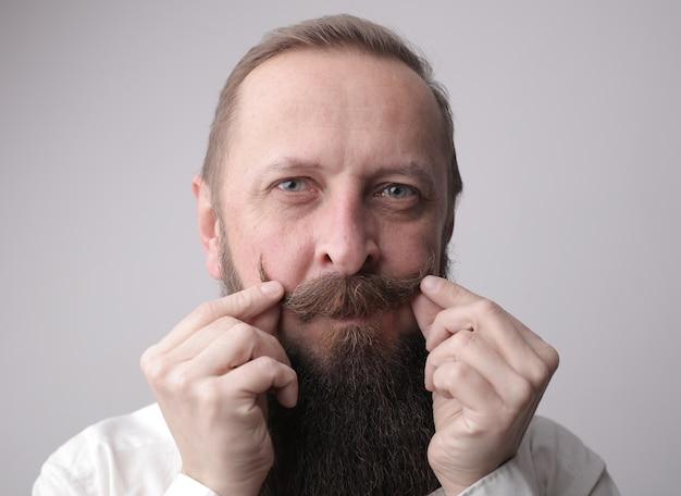 Homme avec une longue barbe et une moustache en souriant debout devant un mur gris