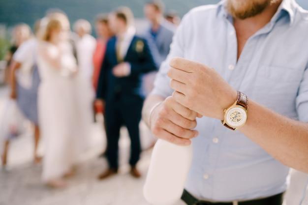 Un homme lors d'une cérémonie de mariage ouvre une bouteille de champagne derrière lui les invités et les jeunes mariés en gros plan