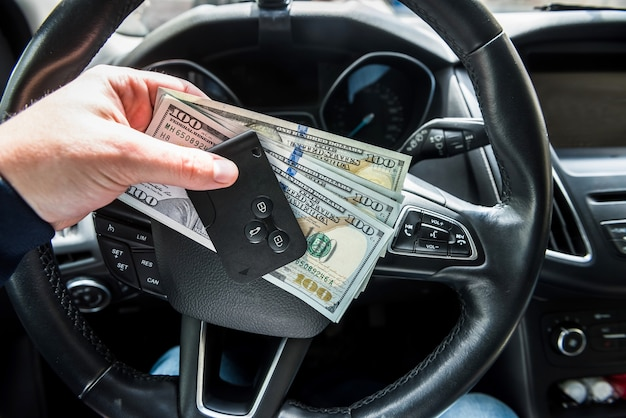 Homme louer une voiture pour le voyage et tenant la clé automatique et dolar. concept de finance
