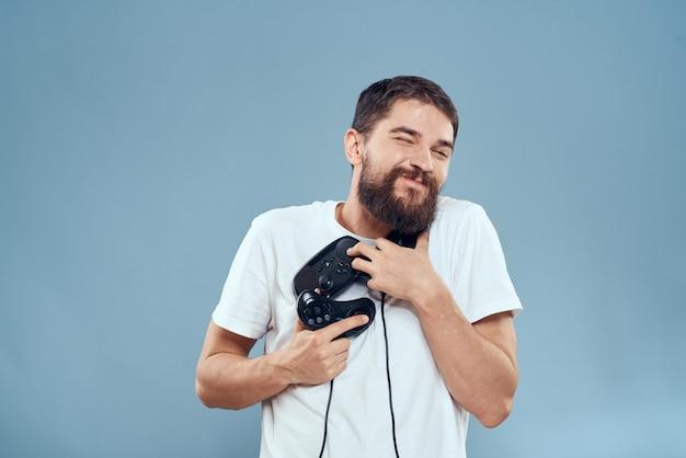 Un homme à lunettes 3d joue à un jeu d'ordinateur dans des consoles avec des joysticks