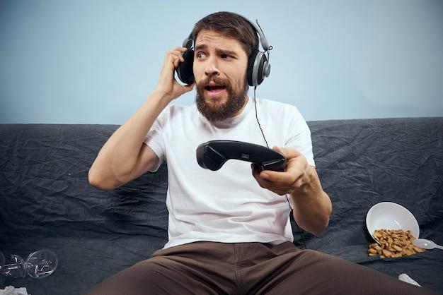 Un homme à lunettes 3d joue à un jeu d'ordinateur dans des consoles avec des manettes de jeu dans des écouteurs sur un canapé à la maison