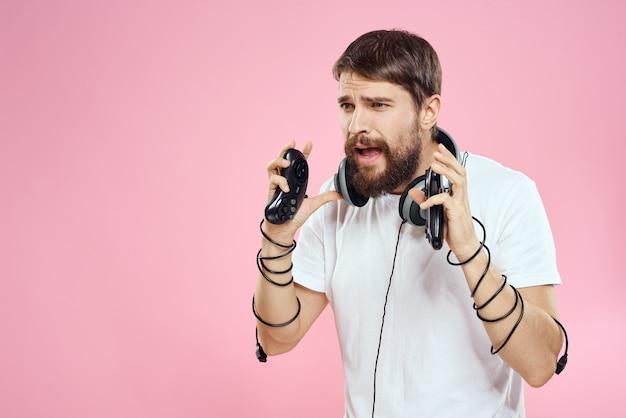 Un homme en lunettes 3d joue à un jeu d'ordinateur dans des consoles avec manettes de jeu