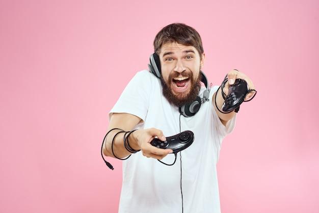 Un homme en lunettes 3d joue à un jeu vidéo dans des consoles avec des manettes de jeu