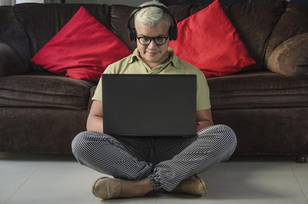 Homme avec des lunettes assis sur le sol du salon à côté du canapé, vérifiant l'ordinateur portable avec des écouteurs