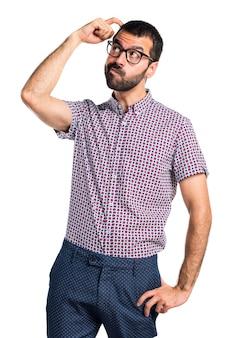 Un homme avec des lunettes ayant des doutes