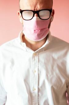 Homme avec des lunettes brumeuses à cause du masque rose