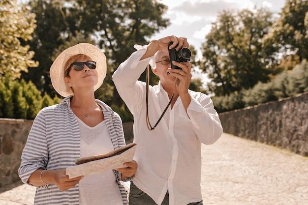 Homme à lunettes et chemise blanche élégante, photographies et sourires avec une femme blonde à lunettes de soleil, chapeau et vêtements frais à rayures avec carte en plein air