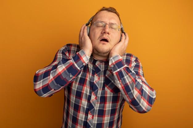 Homme à lunettes et chemise à carreaux avec des écouteurs appréciant la musique debout sur le mur orange