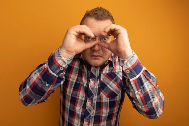 Homme à lunettes et chemise à carreaux faisant un geste binoculaire avec les mains debout sur le mur orange