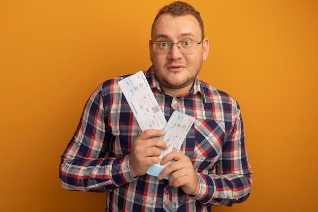 Homme à lunettes et chemise à carreaux tenant des billets d'avion avec une expression de confusion debout sur un mur orange