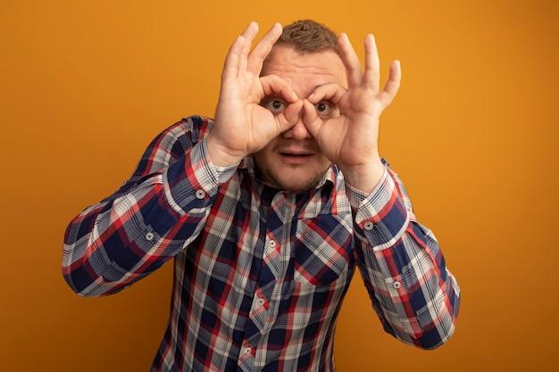 Homme à lunettes et chemise à carreaux à travers les doigts faisant un geste binoculaire debout sur un mur orange