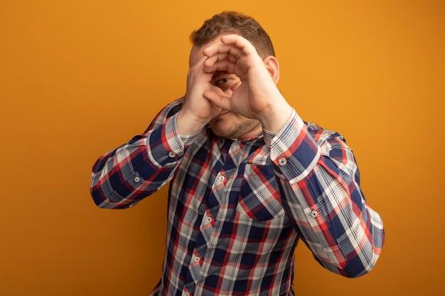 L'homme à lunettes et chemise à carreaux à travers les doigts imitant la lunette debout sur un mur orange