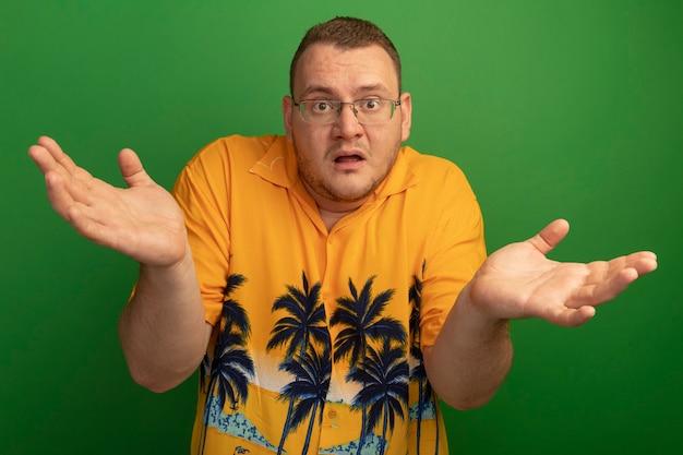Homme à lunettes et chemise orange confondu avec les mains levées debout sur le mur vert