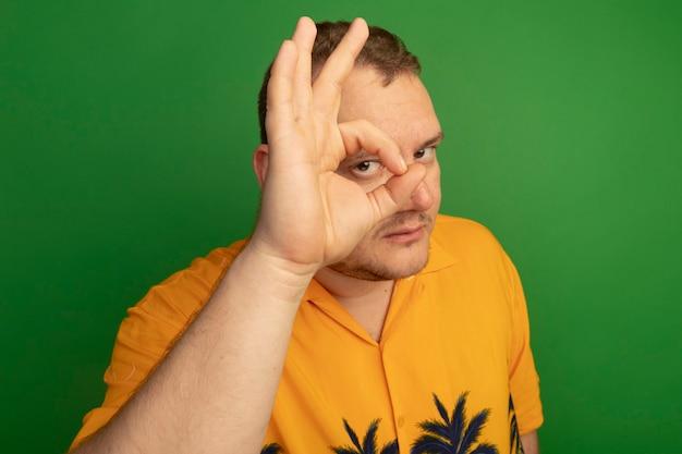 Homme à lunettes et chemise orange faisant signe ok en regardant à travers ce panneau debout sur un mur vert