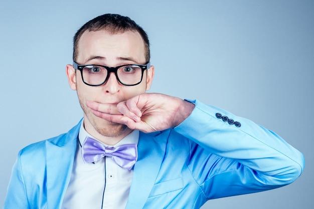 Un homme avec des lunettes et un costume bleu élégant couvre sa bouche avec sa main. le concept de secret, de confidentialité et de vie privée