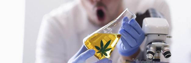 L'homme à lunettes dans des gants en caoutchouc détient flacon avec un liquide jaune en gros plan de laboratoire de chimie