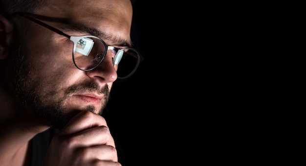 Un homme avec des lunettes dans le noir regarde l'espace de copie d'écran d'ordinateur