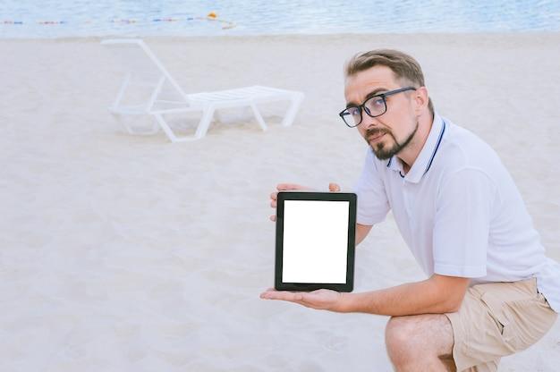 Un homme à lunettes est assis sur la plage avec une maquette d'une tablette dans les mains. dans le contexte d'une chaise longue et de sable avec de l'eau.