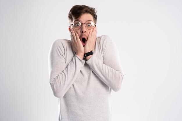 Homme avec des lunettes avec une expression choquée et étonnée.