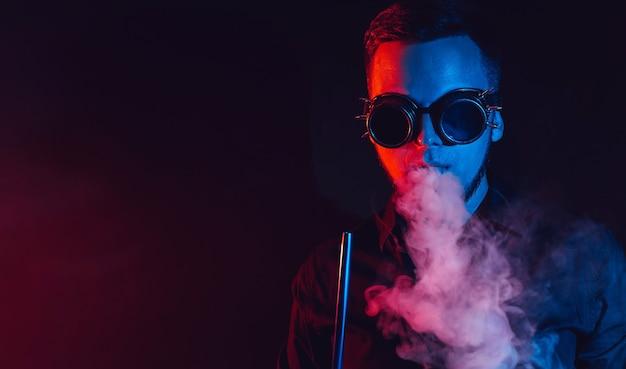 Homme à lunettes fume un narguilé et souffle un nuage de fumée
