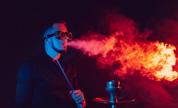 L'homme à lunettes futuristes fume un narguilé et souffle un nuage de fumée dans un bar à chicha avec des néons rouges et bleus