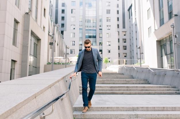 Homme à lunettes marchant sur des escaliers en béton