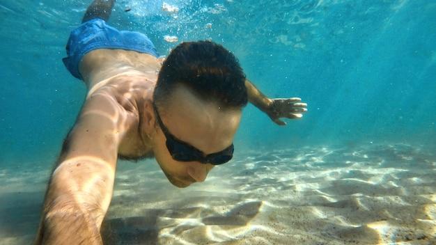 Homme à lunettes nageant sous l'eau bleue et transparente de la mer méditerranée. tenir la caméra