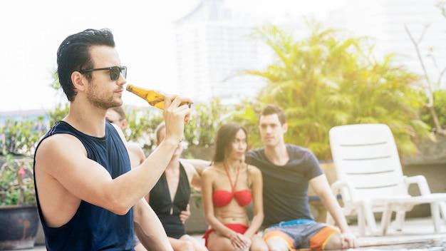 Homme de lunettes noires avec boisson de la bouteille de bière à la piscine avec des amis de garçon et fille dans la suite de fête de bikini.