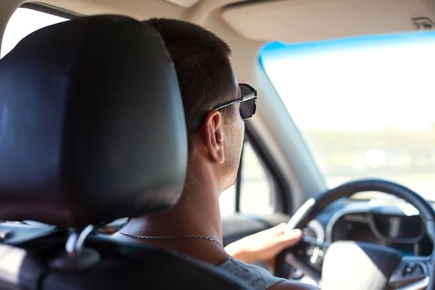 Un homme avec des lunettes noires conduit une voiture. sécurité routière, règles de circulation, déplacements en voiture, navigateur