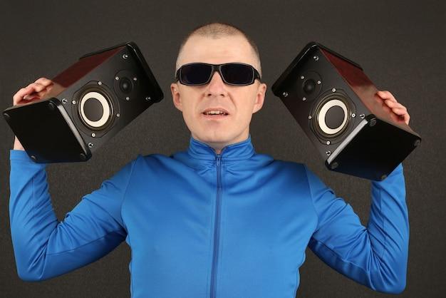 Homme à lunettes noires tenant deux haut-parleurs puissants