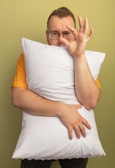 Homme à lunettes portant une chemise orange étreignant un oreiller montrant un geste de petite taille, symbole mesure debout sur mur léger