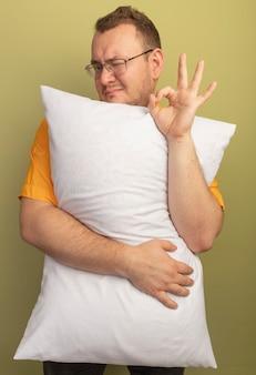 Homme à lunettes portant une chemise orange étreignant un oreiller souriant et clignotant montrant signe ok debout sur un mur léger