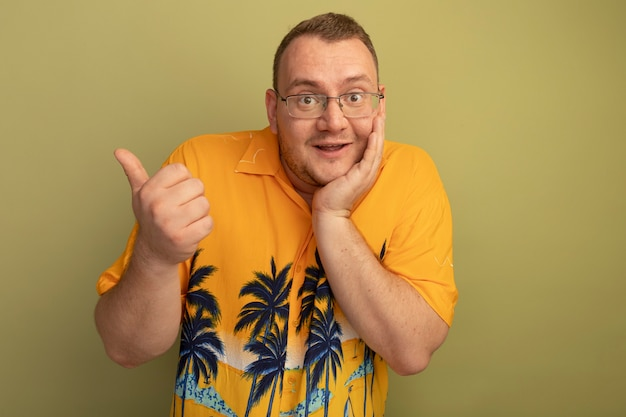 Homme à lunettes portant une chemise orange souriant joyeusement pointant vers l'arrière avec le pouce debout sur un mur léger