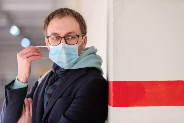 Homme à lunettes portant un masque médical de protection, debout près du mur avec une ligne rouge. épidémie de grippe