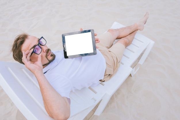 Un homme à lunettes prend un bain de soleil sur la plage sur une chaise longue avec une maquette d'une tablette dans les mains. sur fond de sable.