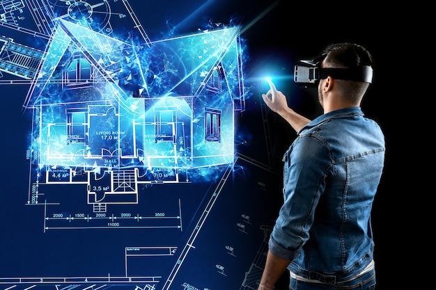 Un homme en lunettes de réalité virtuelle conçoit un bâtiment un hologramme d'une maison
