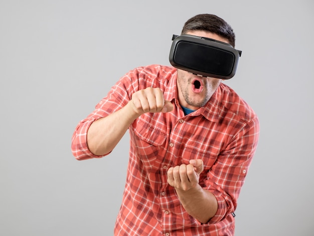 Homme avec des lunettes de réalité virtuelle payant simulateur de voiture