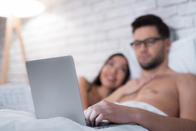 Un homme à lunettes se trouve avec un ordinateur portable et y regarde.