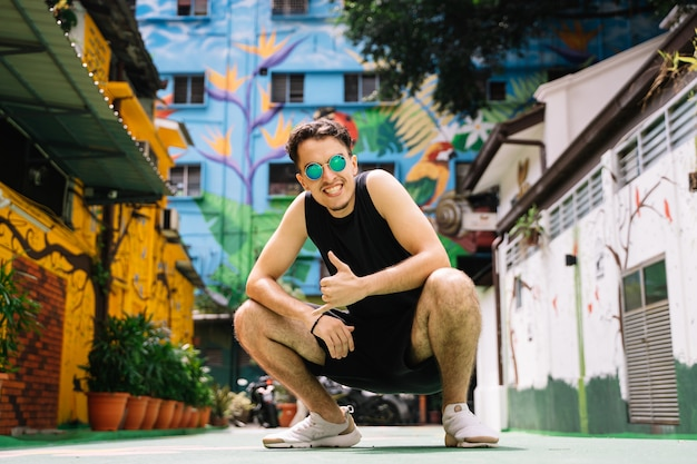 Homme avec des lunettes de soleil accroupi au milieu de la rue avec des bâtiments colorés faisant signe à la main que tout va bien