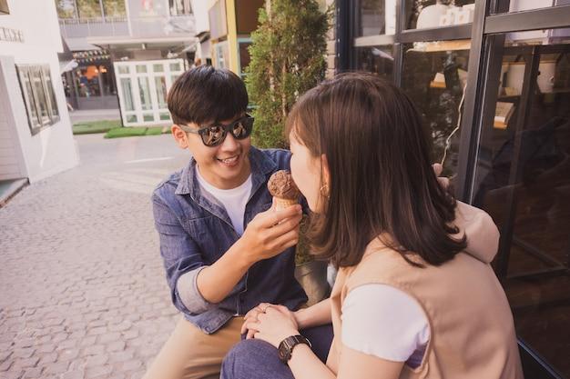 L'homme avec des lunettes de soleil offrant une crème glacée à une femme