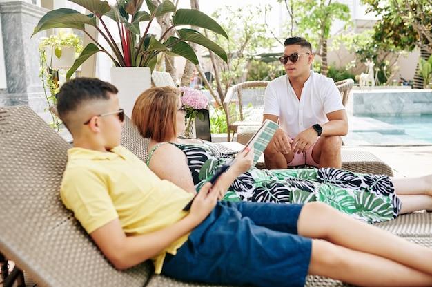 Homme à lunettes de soleil parlant à sa femme et son fils reposant sur des chaises longues près de la piscine
