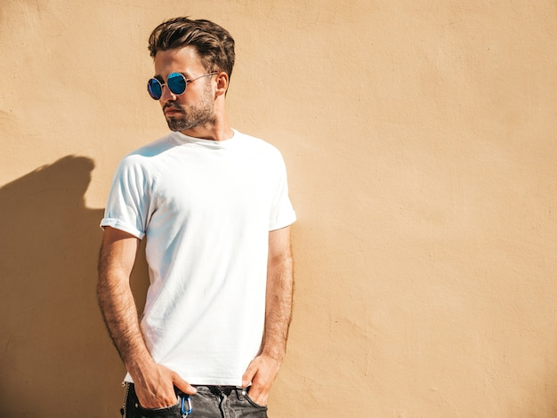 Homme avec des lunettes de soleil portant un t-shirt blanc posant