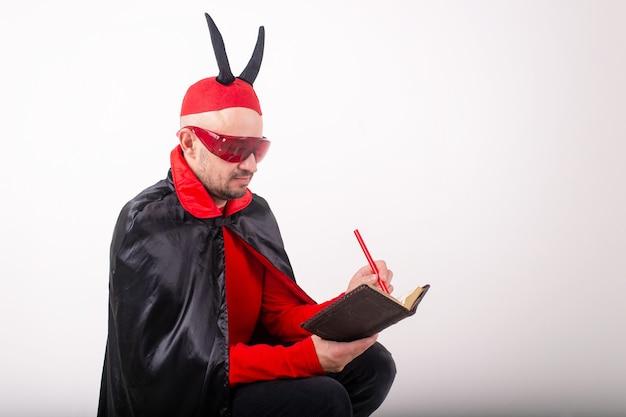Homme en lunettes de soleil rouges et costume d'halloween avec stylo et cahier