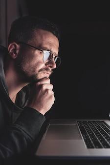 Un homme avec des lunettes travaille sur un ordinateur tard dans la nuit