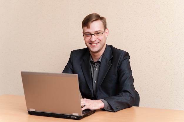 Homme à lunettes travaille pour ordinateur portable